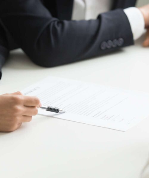 Negotiations about contract terms concept, business partners group considering offer deal discussing conditions at meeting in lawyers office, legal advice, hand pointing at document close up view